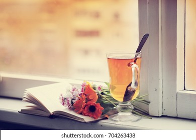 Cozy autumn background with tea ,book and flowers