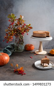 Cozy autumn composition. Chocolate mousse cake on the stand surrounded by autumn leaves and pumpkins on a gray table. Greeting card, cafe, confectionery, bakery, Thanksgiving concept, copy space