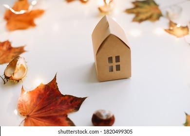 Gemütliche Herbstkomposition. Papierhaus umgeben von Herbstblättern auf einem weißen Tisch. Hyge Lifestyle, gemütliche Herbststimmung. Grußkarte, Herbst, Thanksgiving-Konzept