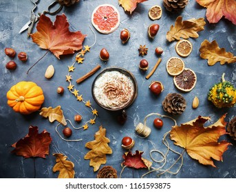 Cozy autumn morning with cup of cocoa with cream and chocolate, dried oranges, cinnamon, nuts and autumn leaves on dark stone background