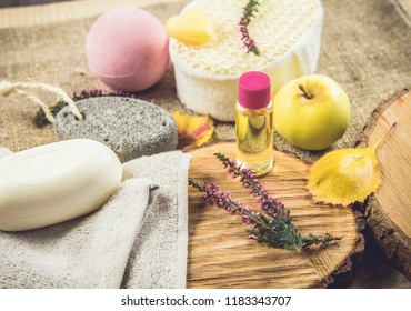Cozy autumn setting with spa essentials for nice relaxing evening. On burlap cloth background are soap bar, massage oil, bath bomb, towel, pumice stone. Seasonal country style.