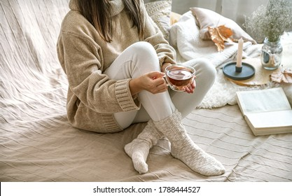 Cozy autumn or winter at home, a woman in a knitted sweater with a Cup of tea and a book .
