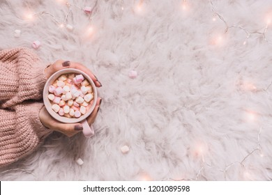 Cozy background. Hands holding mug of hot cocoa or hot chocolate with marshmallow on white rug. Copy space