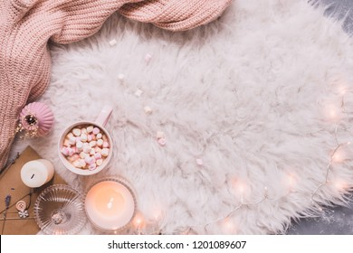 Cozy background. Mug of hot cocoa or hot chocolate with marshmallow on white rug. Copy space.