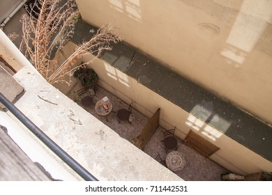 Cozy balconies on the ground floor of a Parisian house decorated with flowers, with several tables (one of them served for breakfast) and some window reflections on the wall — Paris, view from above