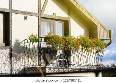 Cozy balcony with sun loungers and flower vases, balcony of the house