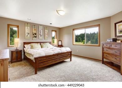 Cozy bathroom interior with double wooden bed and beige carpet floor.
