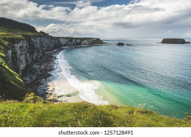 Cozy bay next to the Northern Ireland shoreline. The grass covered cliff washed by the turquoise sea water. Amazing overview of the Irish shoreline. Cloudy sky background. Beauty of the wild nature.