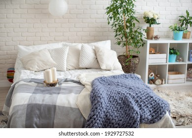 cozy bed with light linens and knitted blankets. Bright bedroom with lots of indoor plants and home decor.The concept of home comfort and recreation.