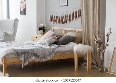 A cozy bed with pillows and blankets in a bright spacious bedroom