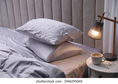 Cozy bed with soft silky bedclothes in light room