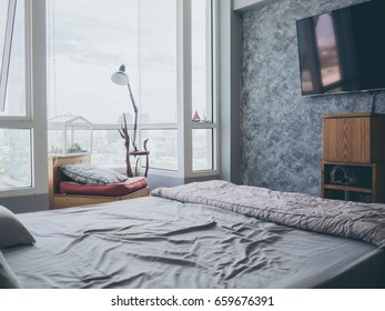 Cozy bedroom apartment with light from big windows glasses.