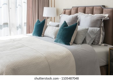 cozy bedroom in classic style with set of pillows and lamp on table side, interior design concept