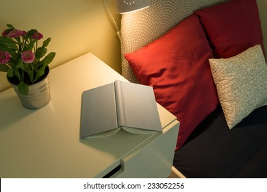 Cozy bedroom interior with book lying on bedside table