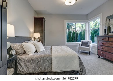 Cozy bedroom interior features soft gray walls framing queen bed dressed in grey and blue bedding and flanked by tall dark brown cabinets. Northwest, USA