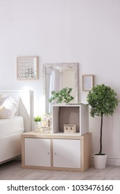 Cozy bedroom interior with shelving unit used as wardrobe