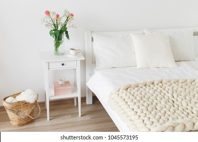 Cozy bedroom interior: white wall, bed with white linen, light beige thick yarn knitted woolen merino chunky blanket or plaid, pillows, bedside table, vase with tulips flowers, wicker basket.