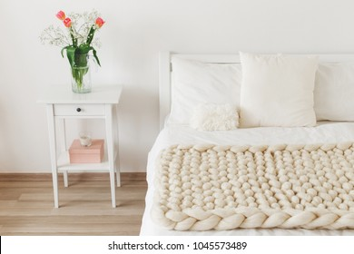 Cozy bedroom interior: white wall, bed with white linen, light beige thick yarn knitted woolen merino chunky blanket or plaid, pillows, bedside table, vase with tulips flowers.