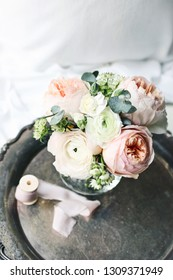 Cozy bedroom still life scene. Wedding, birthday bouquet of pink English roses, Ranunculus and Astrantia flowers and silk ribbon on vintage silver tray.Feminine styled composition. Top view, defocused