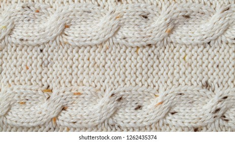 Cozy beige melange yarn knitted texture background. Purl and cables