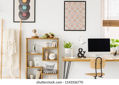 Cozy blanket on a ladder, a wooden bookcase with decorations and posters on a white wall in a hipster bedroom interior with workspace for a teenager