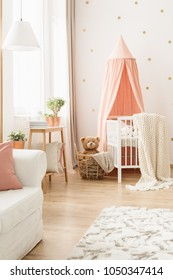 Cozy blanket on a white, modern baby crib with a pink canopy and a teddy bear in a wicker basket in a nursery room interior
