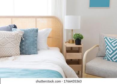 Gemütliches blaues Schlafzimmer mit modernem Interieur, ethnisches Dekor, komfortables Bett, Lampe auf Nachttisch.