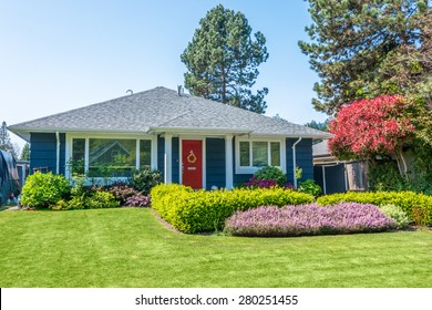Cozy blue house with beautiful landscaping on a sunny day. Home exterior.