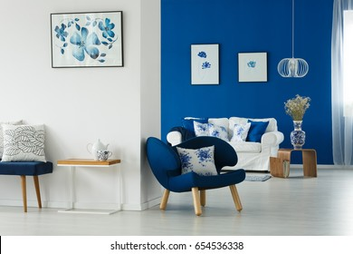 Cozy blue and white living room with flowery patterns on pillows and posters