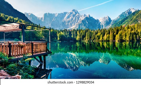 Cozy cafe on the pier. Calm morning view of Fusine lake. Colorful summer scene of Julian Alps with Mangart peak on background, Province of Udine, Italy, Europe. Beauty of nature concept background.