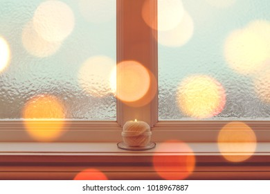 Cozy candle on a windowsill in golden light. Winter holiday mood.