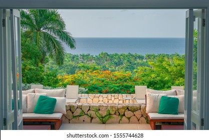 Cozy chairs inside of a beach house with open doors leading a patio, palm trees and the ocean.