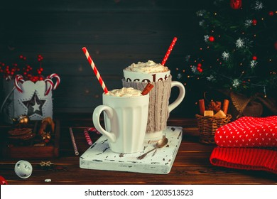 Cozy Christmas composition.Two mug with hot drinks, chocolate with whipped cream and cappuccino with cinnamon stick on a dark wooden background. Sweet treats for cold winter days.