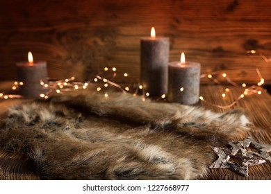 Cozy christmas decoration with candles and fur on a winter evening with short depth of field
