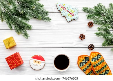 Cozy christmas evening. Coffee, cookies, spruce branch, knitten mittens on white wooden background top view copyspace