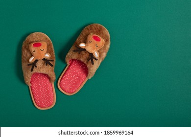 Cozy Christmas slippers on modern green background top view. Christmas celebration at home.