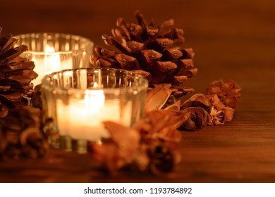 Cozy christmas table decoration, candles and pine cones