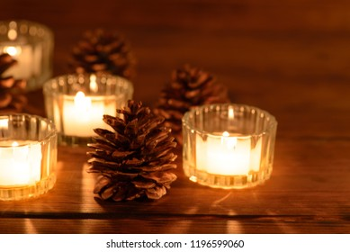 Cozy christmas table decoration, candles and pine cones. Soft focus