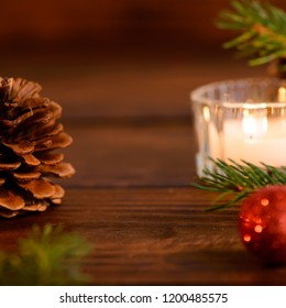 Cozy christmas table decoration, candles, red christmas balls and pine cones