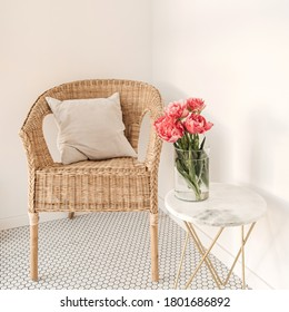 Cozy comfortable home rest space with rattan chair, white wall, mosaic tile, marble table with beautiful peony flower bouquet. Modern interior design concept. Minimalist lounge space
