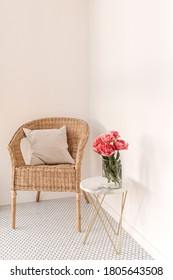Cozy comfortable home rest space with rattan chair, white wall, mosaic tile, marble table with beautiful peony flower bouquet, pillow. Modern interior design concept. Minimalist lounge space