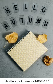 Cozy composition: yellow notebook, leaves, letters Hello autumn on gray background. Top view, flat lay