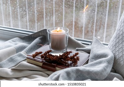 A cozy corner in the house. Candle and rain drops on the window.