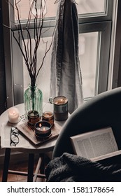 Cozy corner in the living room. Cozy warm blanket. Winter time. Candles on the table. Scandinavian interior decor. Cold winter time. Grey chair, throw blanket. Reading a book. Warm and cozy home