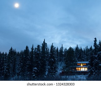 Cozy country living home warmly illuminated isolated in boreal forest taiga moon-lit frozen winter landscape of remote Yukon Territory, YT, Canada