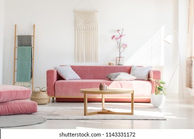 Cozy cushions and stylish textiles in a sunny, feminine living room interior with a pink, velvet sofa and a macrame on a white wall