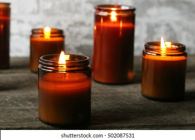 Cozy, Dark, Moody Indoor Scene Of All Natural Soy Candles In Brown Glass Jars Lit And Glowing With Golden Color During The Season Of Fall And Chilly Days