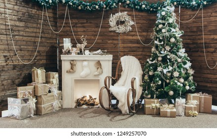 Cozy decor for Christmas and New Year. New Year's Concept. Christmas photo. Christmas scenery photo zone: chair rocking chair, Christmas tree, gifts, fireplace with socks.