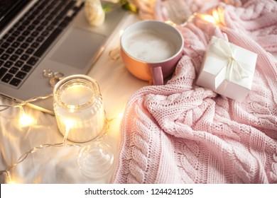 Cozy decor. A cup of cappuccino. Candle in a glass jar, pink knitted blanket, rose, laptop. Cozy. Autumn.