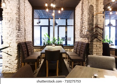 Cozy dining place at window, restaurant background. Beautiful and comfortable interior of cafe seat, copy space.